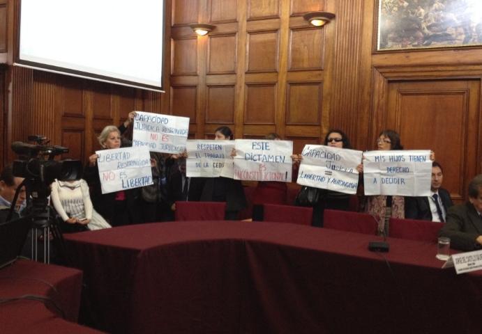 Imagen de representantes de las organizaciones de Perú en una sala, sosteniendo carteles alusivos a los derechos de las personas con discapacidad